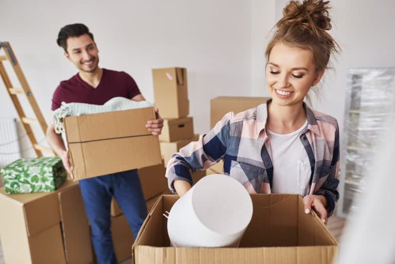 Couple packing their stuff into boxes during move house