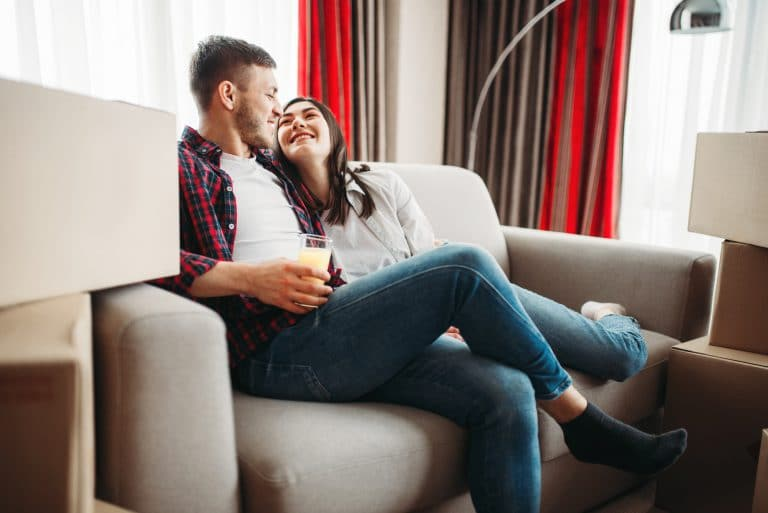 Couple sitting between boxes, moving to new house