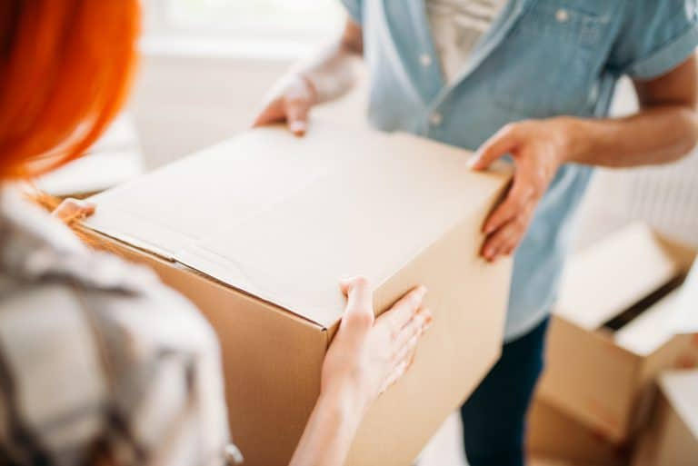Male and female person holds box, housewarming