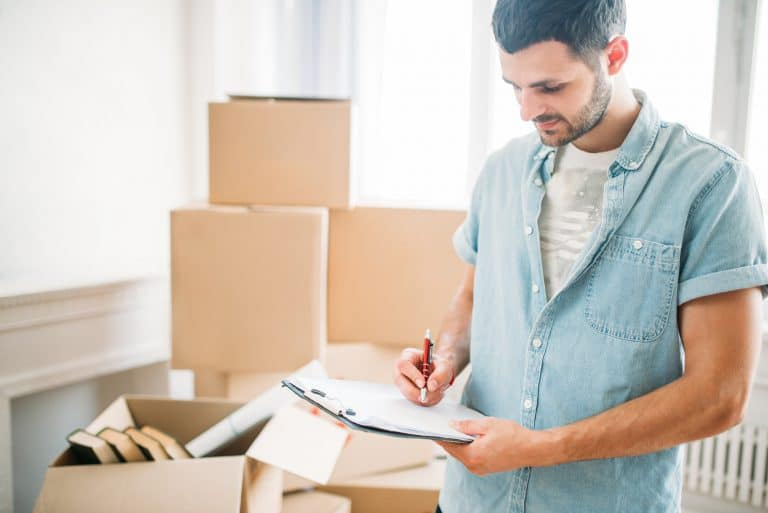 Man with notebook among boxes, housewarming