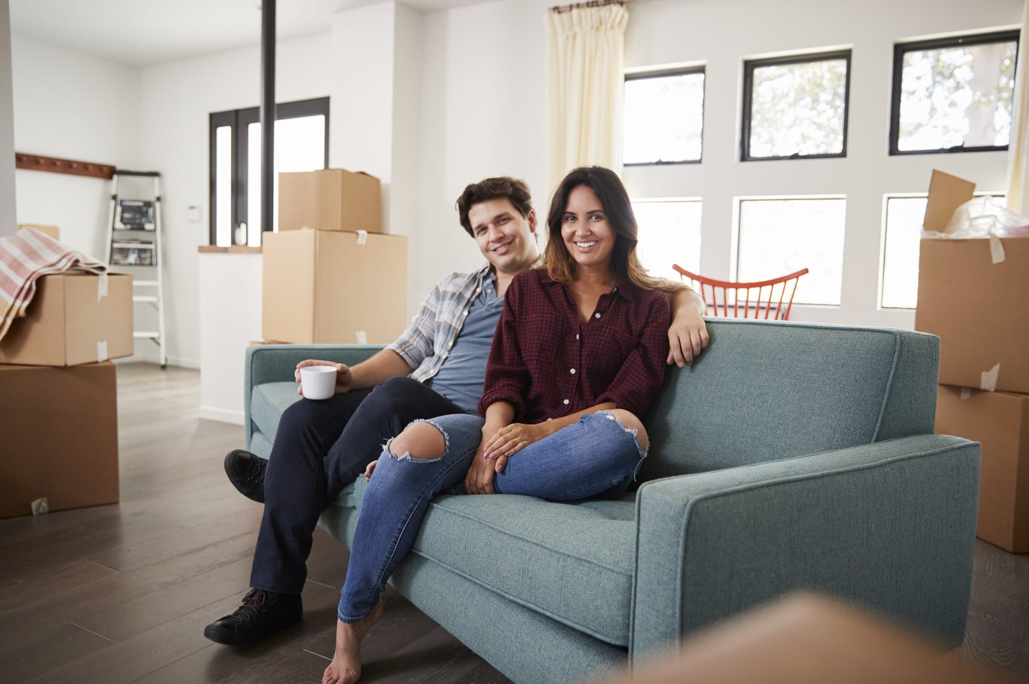 Portrait Of Happy Couple Resting On Sofa Surrounded By Boxes In New Home On Moving Day