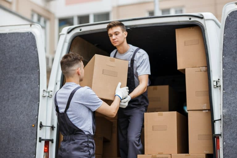 Two moving company employees unloading the van full of boxes.