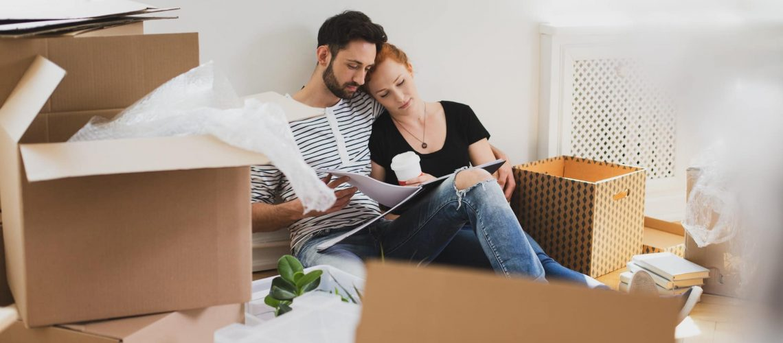 Happy marriage packing stuff into carton boxes while moving-out
