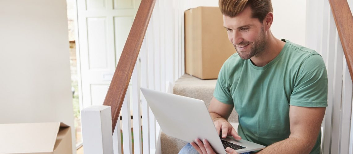 Man Moving Into New Home Looking At Personal Finances On Laptop